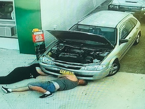 CCTV shows the pair working on the car before the alleged assault.