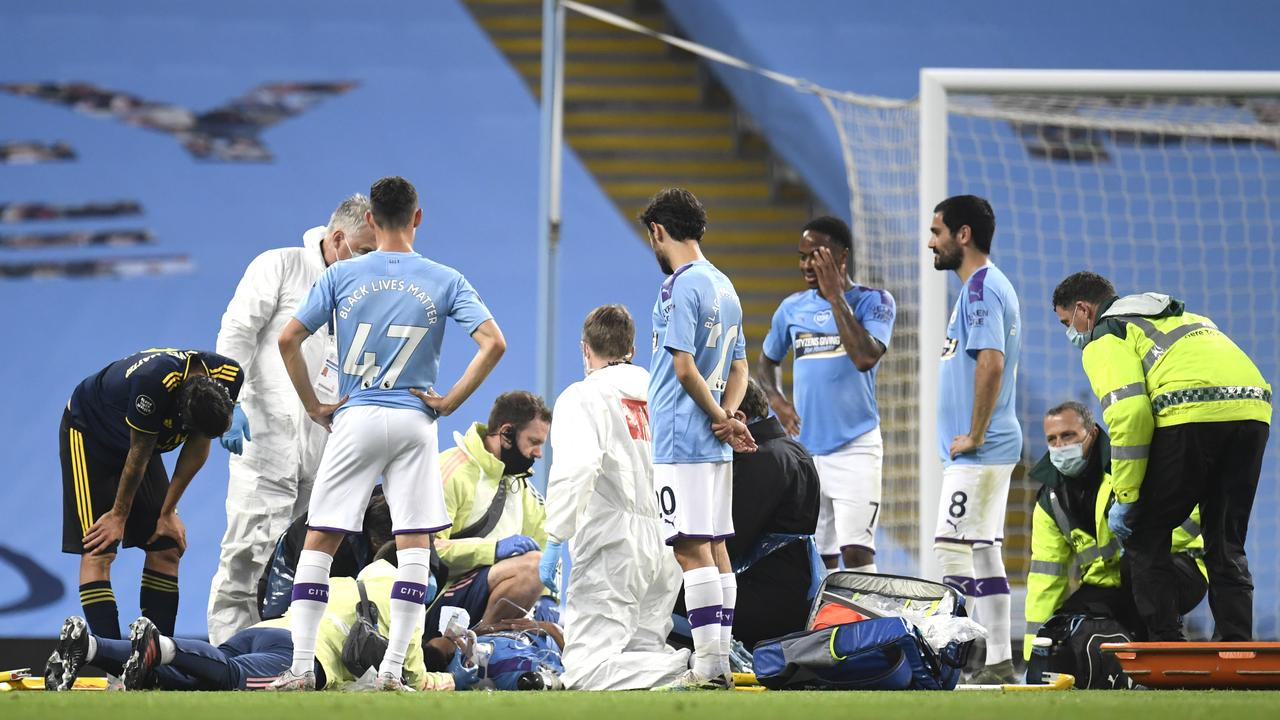 Eric Garcia receives medical treatment as teammates watch on.
