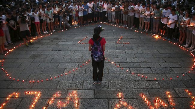 People gather to mourn for the two victims of the Asiana airline plane crash in San Francisco at a park in Jiangshan city in eastern China's Zhejiang province. (AP Photo)
