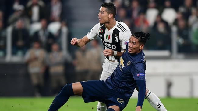 Cristiano Ronaldo is tackled by Smalling.
