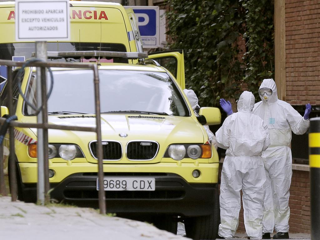 Medical workers wearing protective suits work near the Gran hotel Colon, which has been converted into a medical building to treat COVID-19 in Madrid, Spain. Image: AP