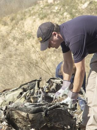 NTSB investigators search through the wreckage. Picture: James Anderson/National Transportation Safety Board via AP.