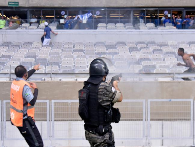 A riot police officer fires tear gas at fans.