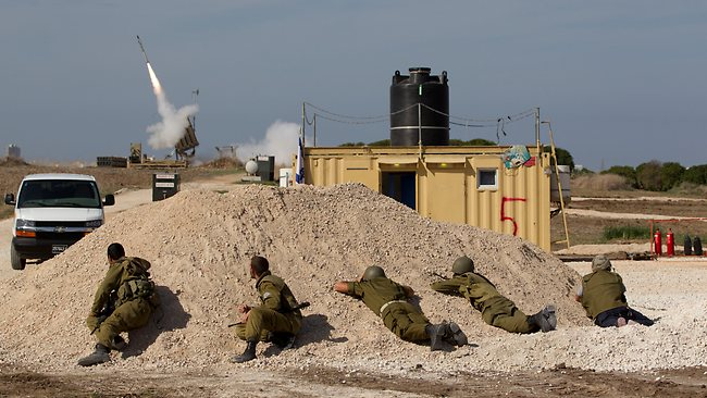 Israeli soldiers look at an Iron Dome missile as it launched near the city of Ashdod, Israel, to intercept a rocket fired by Palestinians militants from Gaza Strip. Picture: Ariel Schalit