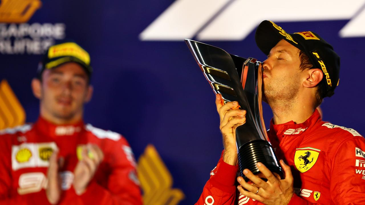 Vettel kisses the trophy as Leclerc watches on.
