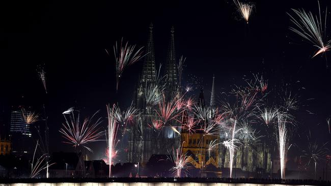 Fireworks explode over the river Rhine in front of the Great Saint Martin Church and the Cologne Cathedral during New Year's celebrations in Cologne on January 1, 2016. Picture: AFP