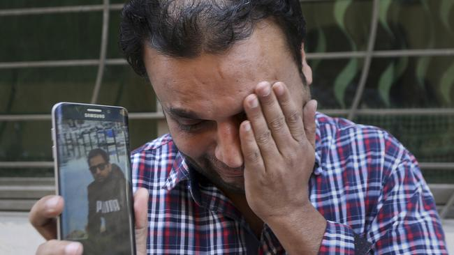 A relative weeps while showing the picture of Sohail Shahid, a Pakistani citizen who was killed in Christchurch mosque shootings. Picture: AP Photo/KM Chaudary
