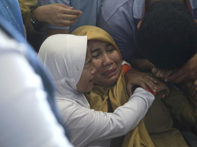 Devastated family members comfort each other as they wait for news on a Lion Air plane that crashed off Java Island at Depati Amir Airport in Pangkal Pinang. Picture: AP