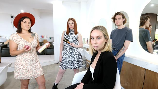 Ashleigh Maguire (centre) the owner of Lujo hair and makeup, with L to R, Desire de Villiers apprentice hairdresser, Chloe Hullick senior hairdresser and Jordan Voss hairdresser, working out if they'll be opening again tomorrow, Lujo hair and Makeup, Teneriffe, Thursday 26th March 2020 – Photo Steve Pohlner