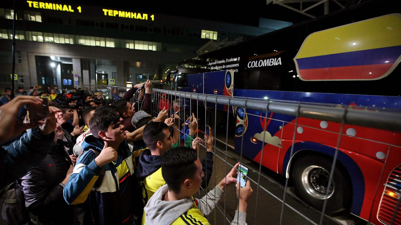 Supporters cheer as the team bus with Colombia's national football team prepares to leave Kazan airport