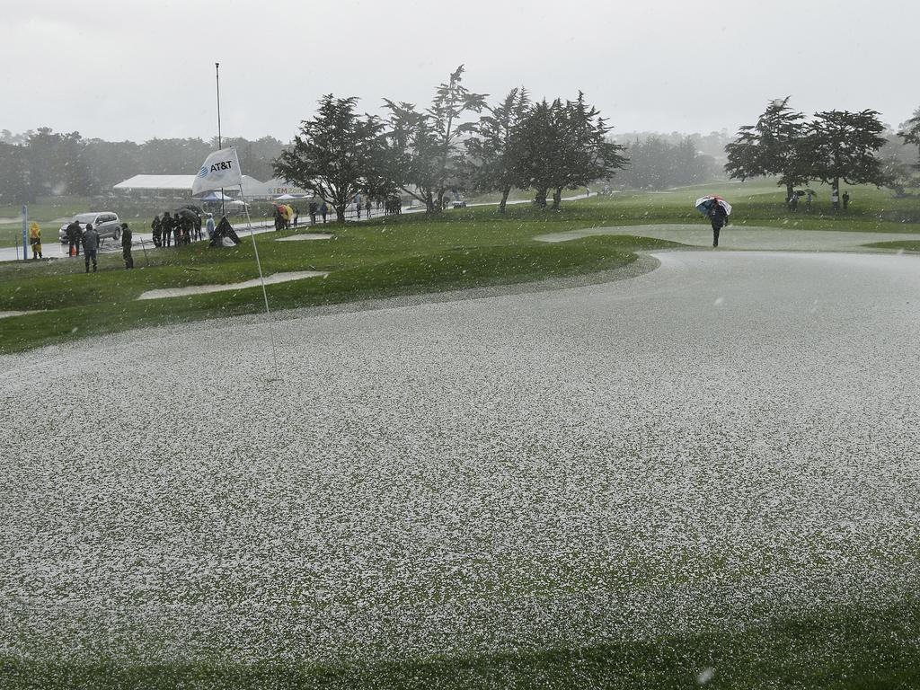 Hail covers the second green of the Pebble Beach Golf Links as a rules official looks on during the final round of the AT&T Pebble Beach Pro-Am golf tournament Sunday, Feb. 10, 2019, in Pebble Beach, Calif. Play was suspended after the hailstorm. (AP Photo/Eric Risberg)