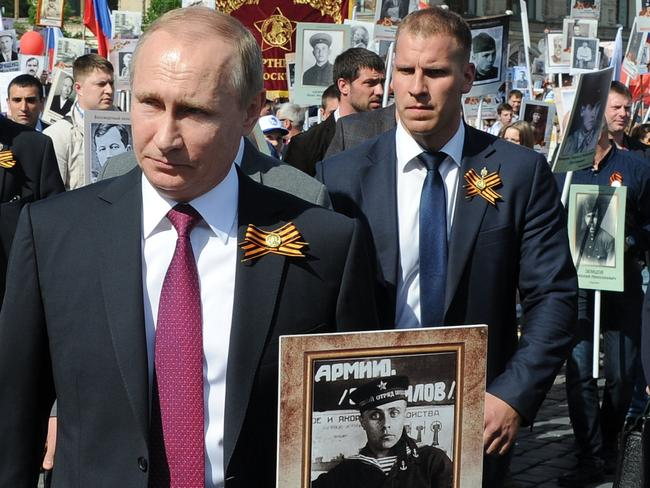 Russian President Vladimir Putin holds a photograph of his war veteran father in a naval uniform during the Immortal Regiment march in Red Square. Picture: Mikhail Klimentyev/Sputnik, Kremlin via AP