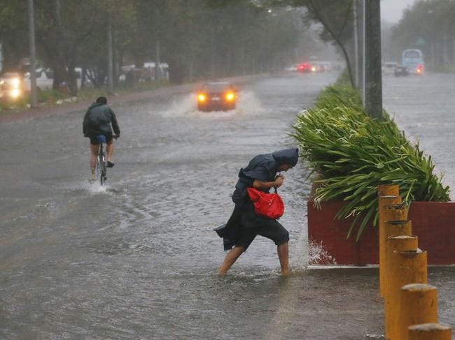 Commuters brave the rain and strong winds brought about by Typhoon Mangkhut which barrelled into northeastern Philippines. Picture: AP