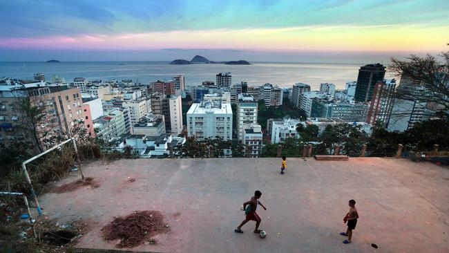 Two kids play football on a dirt pitch overlooking Ipanema in the favela Cantagalo.