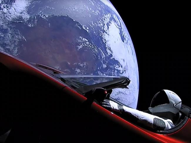 """This still image taken from a SpaceX lifestream video shows """"Starman"""" sitting in SpaceX CEO Elon Musk's cherry red Tesla roadster after the Falcon Heavy rocket delivered it into orbit around the Earth."""