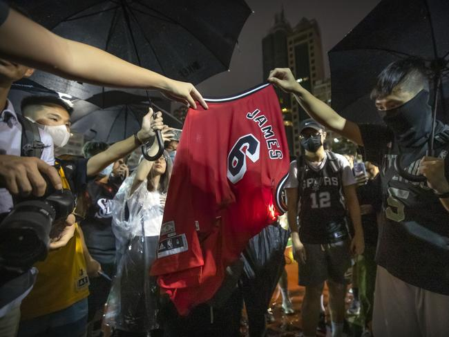 Demonstrators set a LeBron James jersey on fire during a rally at the Southorn Playground in Hong Kong. (AP Photo/Mark Schiefelbein)