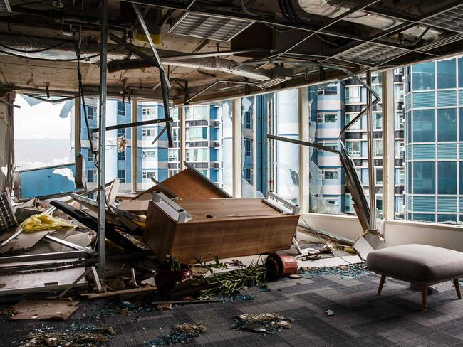Panels and debris from a collapsed ceiling are seen with blown over pieces of furniture in a company office in Hong Kong. Picture: AFP