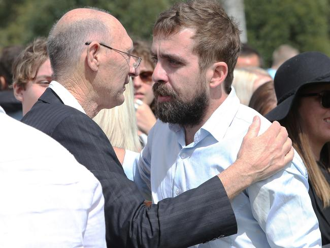 Ms Easey's brother Brendon (right) is comforted by a fellow mourner at his sister's funeral. Picture: Peter Lorimer