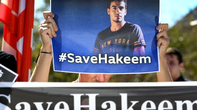 People hold up banners at a rally in Melbourne on February 2, 2019, supporting Bahraini refugee footballer Hakeem al-Araibi. Picture: William WEST / AFP.