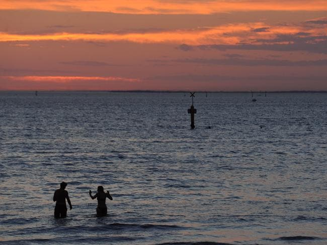 Beach lovers watch the sunset over Port Phillip Bay between St Kilda and Port Melbourne. Picture: Andrew Henshaw