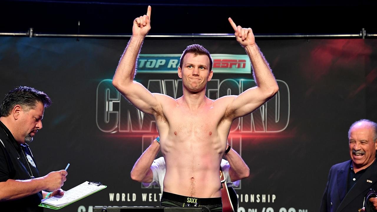 WBO welterweight champion Jeff Horn poses on the scale as he makes weight on his second attempt.