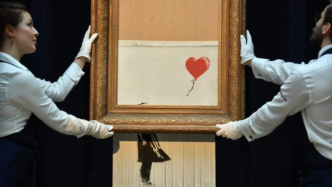 "Sotheby's employees pose with the newly completed work by artist Banksy entitled ""Love is in the Bin"" in London on October 12, 2018 (Photo by Ben STANSALL / AFP)"