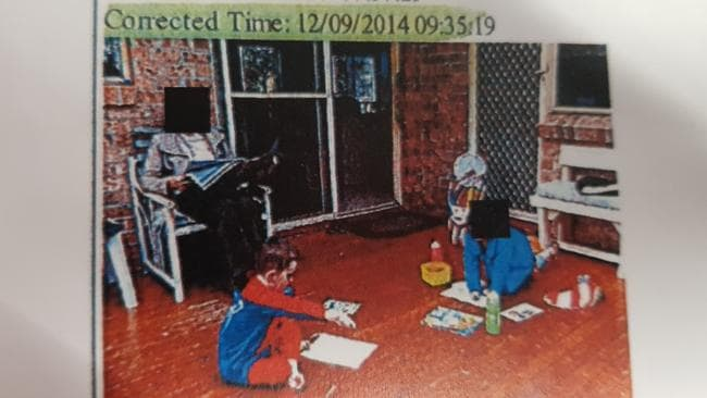 William Tyrrell bends over a picture book playing opposite his sister while their foster grandmother reads in a chair.