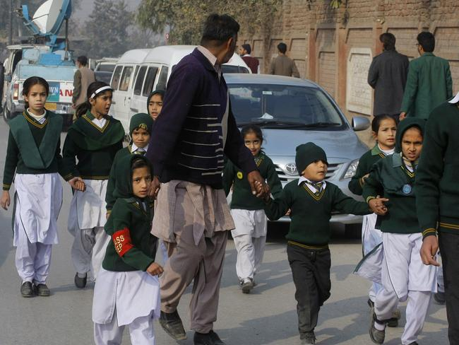 Safely out ... A plainclothes security officer escorts students rescued from a nearby school during the attack. Picture: AP/Mohammad Sajjad