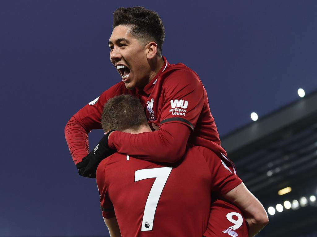 Liverpool's Brazilian midfielder Roberto Firmino (up) celebrates with Liverpool's English midfielder James Milner after Liverpool's Egyptian midfielder Mohamed Salah (not pictured) scores their third goal during the English Premier League football match between Liverpool and Crystal Palace at Anfield in Liverpool, north west England on January 19, 2019. (Photo by Paul ELLIS / AFP) / RESTRICTED TO EDITORIAL USE. No use with unauthorized audio, video, data, fixture lists, club/league logos or 'live' services. Online in-match use limited to 120 images. An additional 40 images may be used in extra time. No video emulation. Social media in-match use limited to 120 images. An additional 40 images may be used in extra time. No use in betting publications, games or single club/league/player publications. /