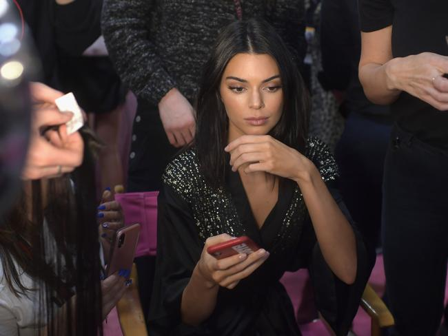 Kendall Jenner, wondering which hashtag she is going to use on her Instagram post.