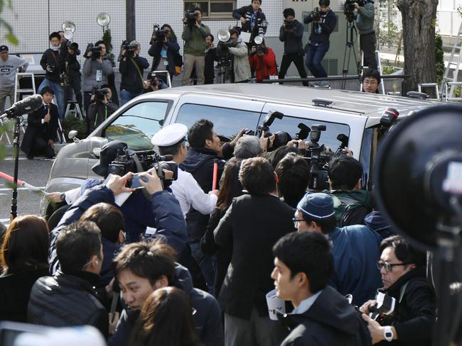 Photographers surround a police van transporting Takahiro Shiraishi, whose gruesome deeds both repel and fascinate the Japanese public. Picture: AFP.