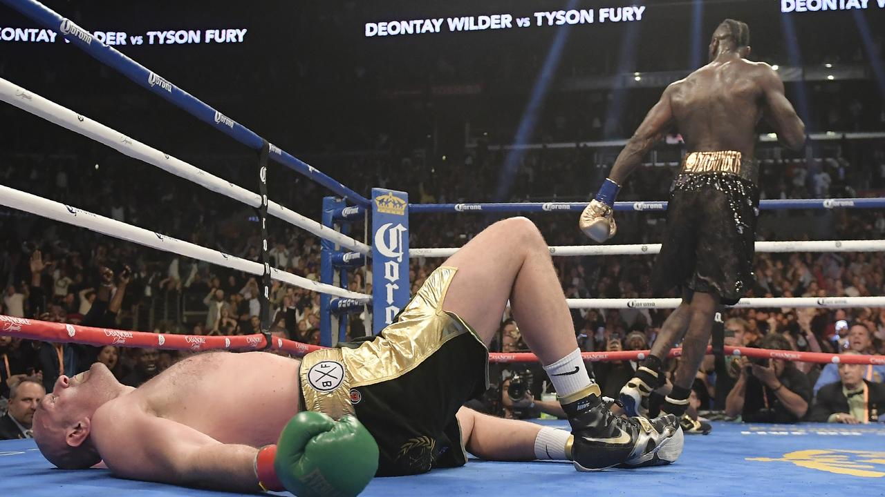 Tyson Fury lies on the canvas after being knocked down by Deontay Wilder during the 12th.