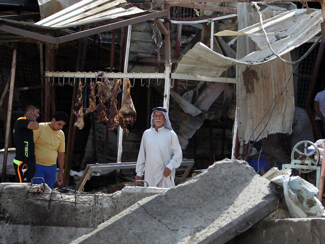 Bomb blast ... the explosion destroyed structures but left meat hanging in the market. Picture: AFP PHOTO / AHMAD AL-RUBAYE