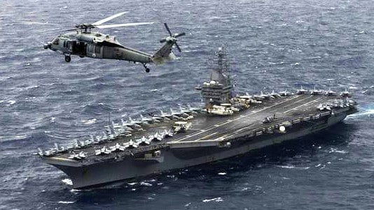 An MH-60S Sea Hawk Helicopter hovers above the aircraft carrier USS Nimitz in the Bay of Bengal in 2017. Picture: US Navy