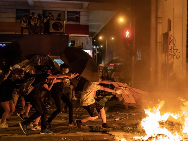 A pro-democracy protester throws cardboard at a burning barricade outside of Mongkok Police Station. Picture: Getty