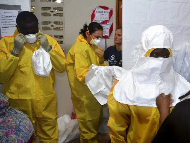 Front line ... Staff for the Christian charity Samaritan's Purse putting on protective gear in the ELWA hospital in the Liberian capital Monrovia. An American doctor battling West Africa's Ebola epidemic has himself fallen sick with the disease in Liberia, as has an aid worker.