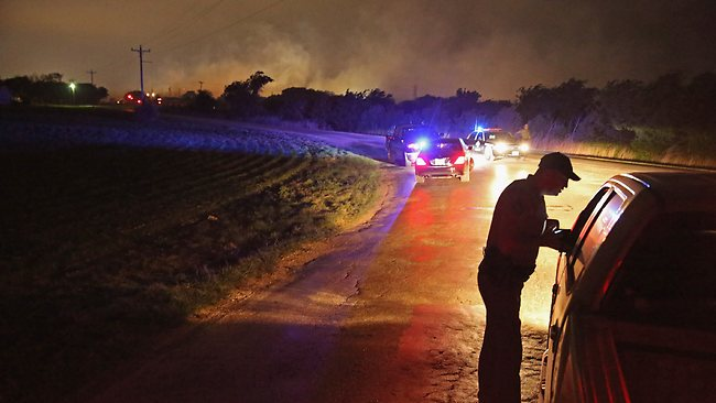 With smoke rising in the distance, a law enformcement officer runs a check point at the perimeter about half a mile from the West Fertilizer Company April 18, 2013 in West, Texas. AFP Photo