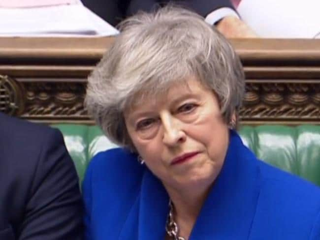 UK Prime Minister Theresa May listens to a question in parliament before the start of the no-confidence debate.