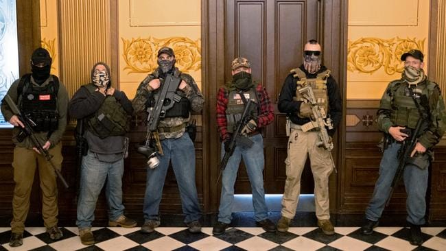 A militia group with no political affiliation from Michigan stands in front of the Governor's office after protesters occupied the state capitol building on April 30.