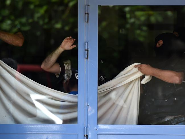 Terror swoop ... French special forces cover a window with a sheet as they search the apartment of the suspect as Yacine Sali. Picture: Philippe DesMazes/AFP
