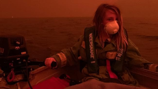 Finn Burns escapes the fires in a boat on Mallacoota lake in one of the most iconic images of the devastating bushfire season. Picture: ABC Gippsland