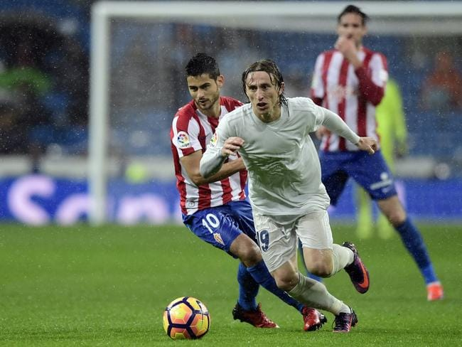Real Madrid's Croatian midfielder Luka Modric (R) vies with Sporting Gijon's midfielder Nacho Cases.