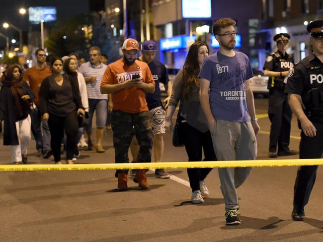 Civilians are escorted from the scene of a shooting in Toronto. Picture: AP
