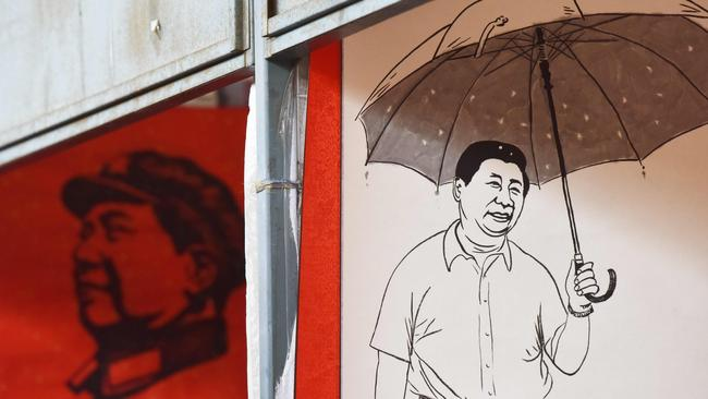 Posters of Mao Zedong, left, and the Chinese President at a Beijing market last month. Picture: AFP