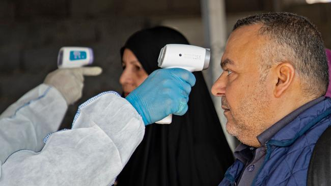 A medical team takes the temperature of Iraqi travellers at the Shalamjah border crossing upon their return from Iran on February 21, 2020. Picture: Hussein Faleh/AFP