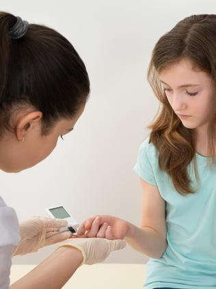 A doctor measuring a girl's blood sugar level. Picture: iStock