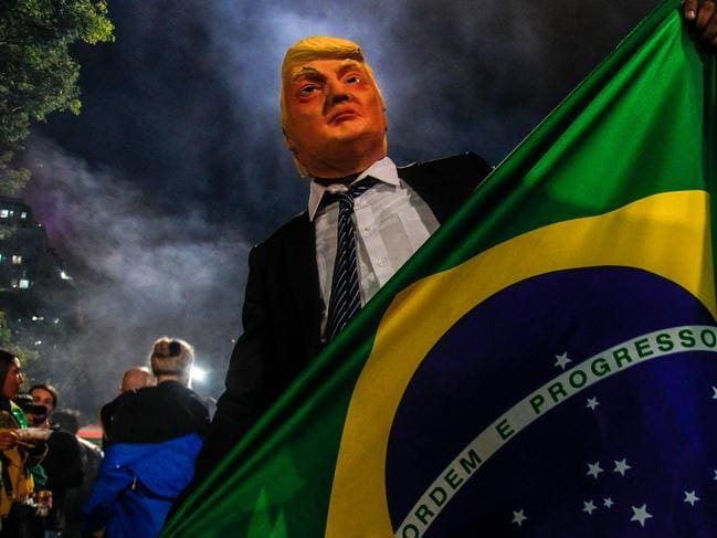 A supporter of far-right lawmaker, Jair Bolsonaro, wears a mask of US President Donald Trump as he celebrates Mr Bolsonaro's win. Picture: AFP