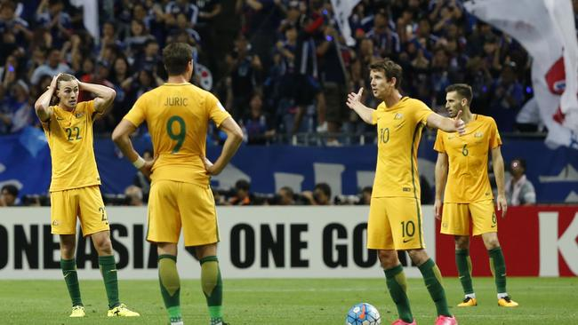 Australia's team players react after Japan scored.