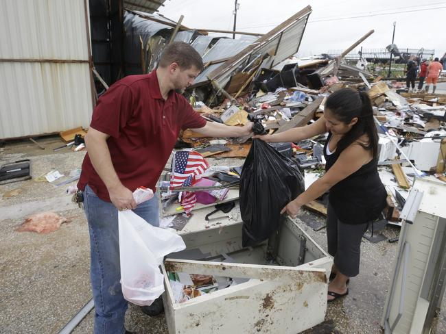 Kenneth Byrant and his wife, Jennifer Byrant, search through debris from Bryant's Auto Sales in Katy, Texas after a possible tornado during Hurricane Harvey. Picture: Melissa Phillip /Houston Chronicle via AP