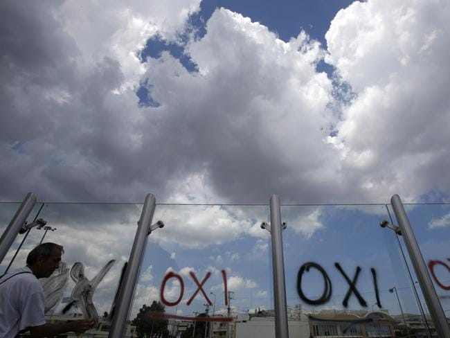 Protest ... a worker cleans the word ''NO'' written in Greek, graffitied on a train station wall, ahead of a referendum. Picture: AP Photo/Thanassis Stavrakis